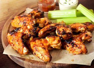 Delicious chicken wings on a wooden cutting board. Close-up shot of tasty chicken wings with perennial celery, sour cream dip and bbq sauce.