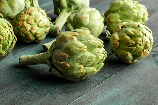A closeup of a globe artichoke on a dark wooden background with copy space