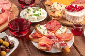 Wine tasting and pairing. Wineglasses with cheese sandwiches and a cheese platter on a dark wooden background