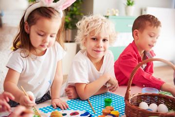 Happy kids start decorating easter eggs