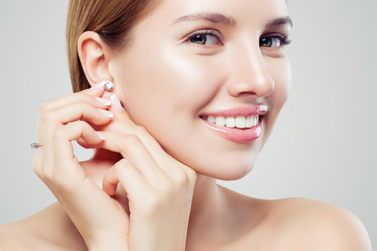 Closeup portrait of jewelry model. Beautiful woman with diamond earrings and ring, face closeup