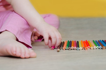 child playing with colored pencils