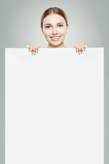 Cheerful woman with white empty paper board background. Pretty girl smiling
