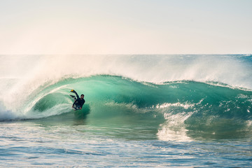 surfer riding a perfect barrel of a wave at sunset