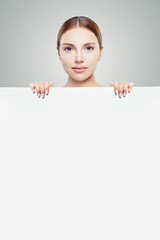 Pretty woman showing white empty paper banner background and looking at camera, studio portrait
