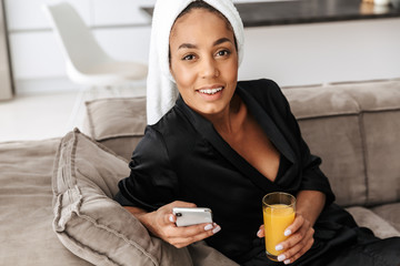 Portrait of gorgeous african american woman wearing housecoat, using mobile phone and drinking juice at home