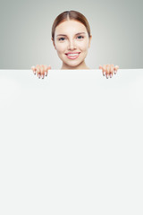 Smiling model woman holding white empty paper board background with copy space for offer and infographics
