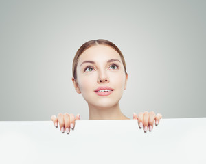 Healthy woman looking up and holding white empty paper board background with copy space for advertising marketing or product placement