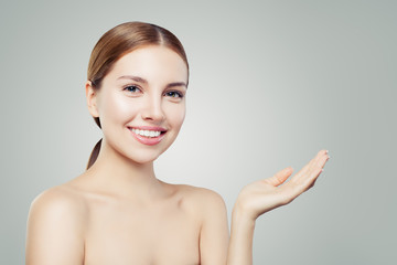 Pretty woman smiling and showing empty open hand. Facial treatment, face lifting, anti aging and skin care cosmetics concept.