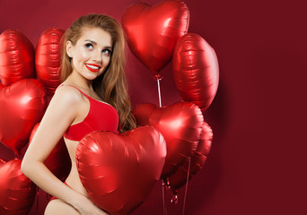 Sexy woman in red underwear on red balloons heart background with empty copy space. Surprise and Valentine's day concept