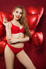 Excited sexy woman with balloons red heart. Happy girl in red underwear on red balloons red heart background. Surprise, valentines people and Valentine's day concept