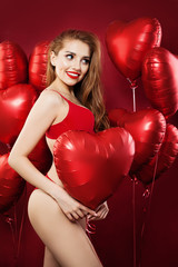 Happy woman with balloons red heart. Sexy girl in red underwear. Valentine's day concept . Positive emotion. Expressive facial expressions