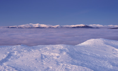 View to snowy mountains range above the clouds