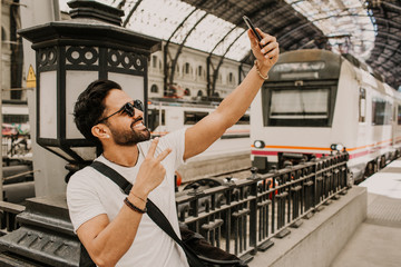 Content attractive hispanic male in white tshirt photographing himself on mobile phone while waiting train on railway station.Bearded hipster male making selfie via smartphone on rail platform