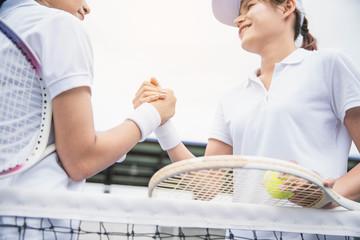 Women tennis player handshaking after playing a tennis match. Handshake at tennis court - agonism,respect,fair play,sport concept.