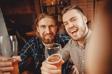 Selfie time. Two bearded hipster friends relax bar, take pictures on phone, drink beer and smile widely. Photo networks