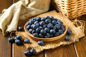 Fresh blueberries in wooden plate on a wooden table
