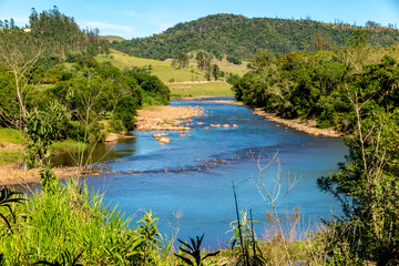 Wide and calm river, with stones and a lot of vegetation in the margins, under blue sky, city of Pedras Soltas, Santa Catatarina, Brazil