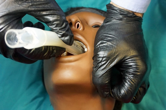 Medical manipulation for airway management. Laryngeal mask airway insertion by stuff in a black gloves on a simulation mannequin dummy during medical training. ACLS.