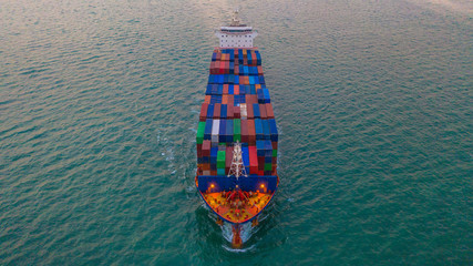 Cargo freight ship carrying container box for import and export business logistic and transportation by cargo ship in open sea, Aerial view.