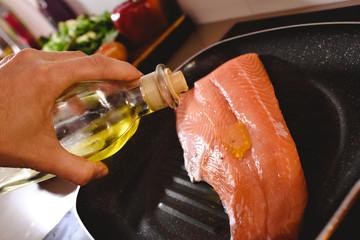 Raw salmon fillet in the pan, cook pouring olive oil over it to cook it.