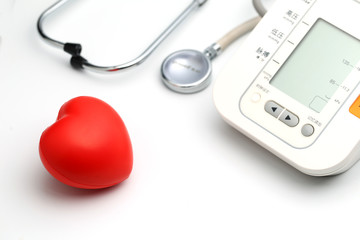 Sphygmomanometer, red heart and stethoscope on white table, close up view