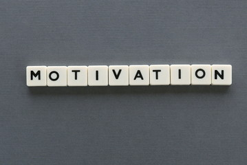 Motivation word made of square letter word on grey background.
