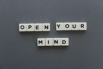 Open your mind word made of square letter word on grey background.