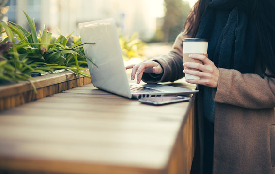 Young cute woman with laptop and coffee outdoor on wooden urban terrace