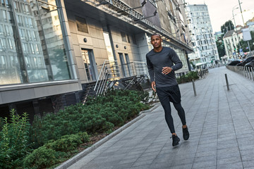 Morning workout. Young and strong african man in stylish sportswear running in the city