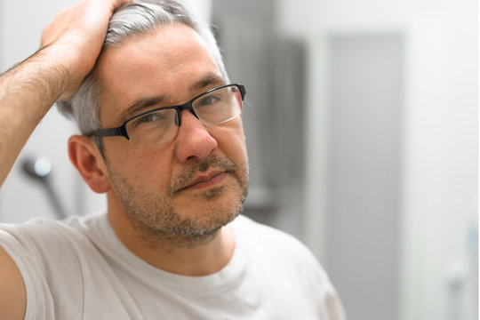 portrait of middle aged gray haired man with glasses in bathroom