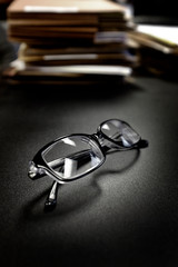 Glasses on Desk With Files Business Education Folders Papers