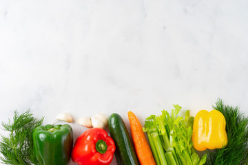 White background with a border of fresh vegetables. Top view.