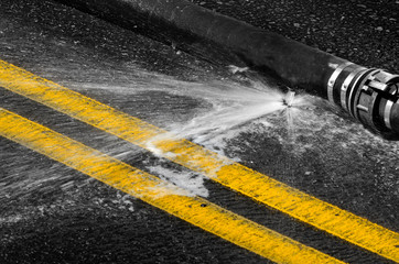 Fire Hose Leaking on Pavement of Road with Double Yellow Lines
