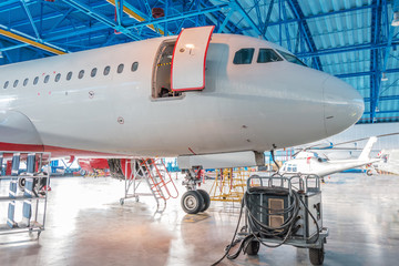 The nose of the aircraft fuselage with open door in the aircraft hangar.