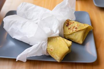 two yellow pancake wtih filling on blue plate