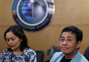 Rappler's CEO Maria Ressa and managing editor Glenda Gloria wait inside the National Bureau of Investigation in Manila