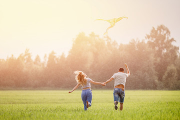 Running on grass lovers. Woman looks up at flying kite. Blurred background.