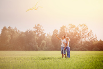Happy couple flying kite. Woman stands behind man back and hugs guy.