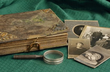 Old photo album and historical photos of family on a green tablecloth.