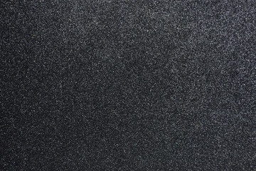 Bumpy black glitter textured background, Closeup