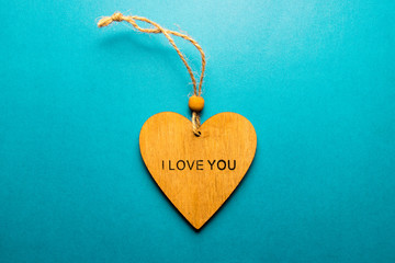 """A wooden heart with the words """"I love you"""", flat lay on a turquoise background, space for your records"""