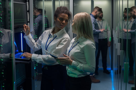 Two women are working in a data center with rows of server racks