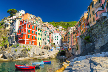 Riomaggiore traditional typical Italian fishing village in National park Cinque Terre with colorful multicolored buildings houses on hill and boats on water, clear blue sky background, Liguria, Italy
