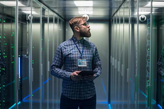 Adult bearded engineer in server room