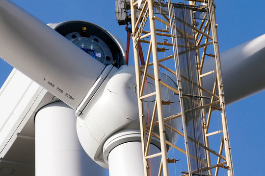 A worker is seen as a crane lifts a propeller to the top of a power-generating windmill turbine in a wind farm in Graincourt-Les-Havrincourt,
