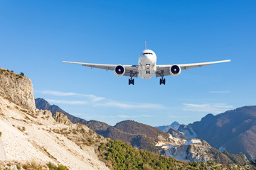 Mountain landscape and landing passenger aircraft. Travel to the mountainous countries