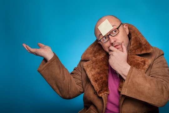 An elderly bald man in a fur coat has a blank post it on the forehead