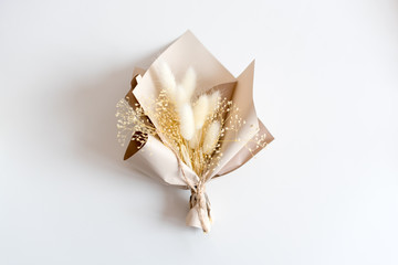 Dried flowers in minimalist bouquet on light background. Flowers composition. Flat lay, top view, copy space. Love, spring and gift concept.
