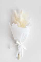 Dried flowers in minimalist bouquet on light background. Flowers composition. Flat lay, top view. Love, spring and gift concept.